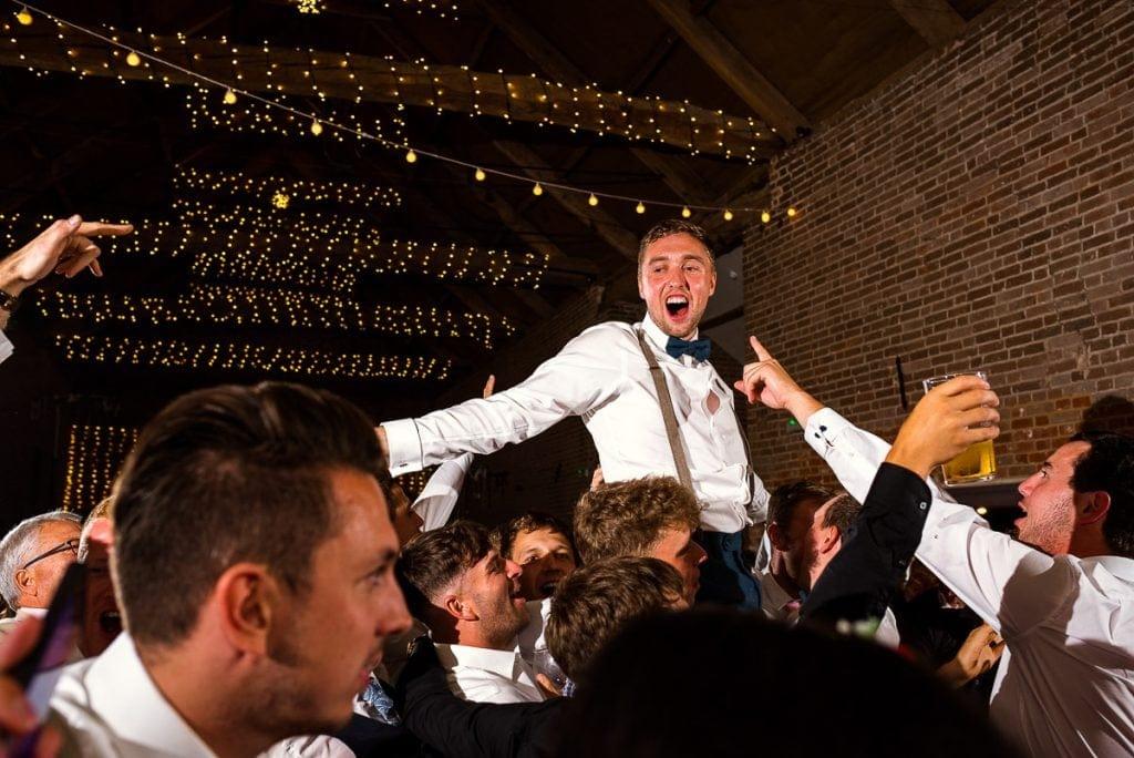 Groom held aloft during wedding reception partying