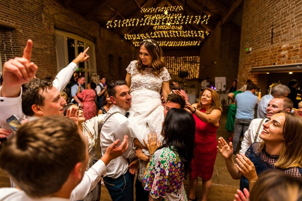 Bride being carried aloft during wedding reception at Manor Mews